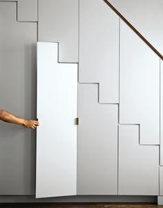 Hidden storage stairwell with raw brass hardware - A Prospect Heights apartment's main stairwell.  Photo by Matthew Williams