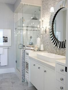 chic, modern blue & gray bathroom design with round beveled mirror, overmount vessel porcelain sink, polished chrome fixtures, white bathroom cabinets, chrome hardware, frameless glass shower, rainfall shower head, ribbed cotton towels, soft gray blue wall color paint