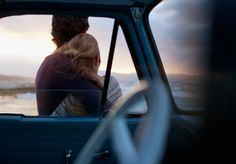 Stock Photo : Hugging couple leaning against car and looking at ocean view
