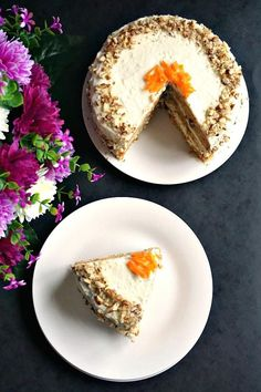 Overhead photo of a slice of cake in a white plate and a whole cake on another white plate with flowers on the left hand side of the photo
