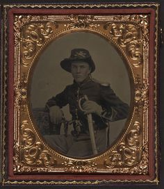 [Unidentified soldier in Union uniform with gauntlets, shoulder scales, and cavalry Company K Hardee hat holding dual Colt Model 1855 Root sidehammer pistols and cavalry saber] [between 1861 and 1865] 1 photograph : sixth-plate tintype ; 9.3 x 8 cm (case) Notes: Title devised by Library staff. Case: Leather oval scroll design. Gift; Tom Liljenquist; 2010; (DLC/PP-2010:105). Subjects: United States.--Army--People--1860-1870. Soldiers--Union--1870-1880. Military uniforms--Union--1870...