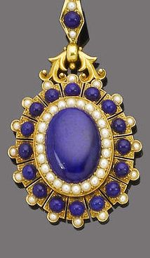 A late 19th century gold, seed pearl and lapis lazuli pendant, circa 1870.  The pendant set to the centre with an oval cabochon lapis lazuli within a seed pearl border, to a splayed lapis lazuli and seed pearl surround, glazed compartment to the reverse.
