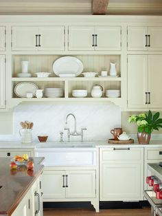 Crisp white marble on the perimeter countertops and behind the sink highlight the similar tone of the traditional farmhouse-style basin. A satin-nickel bridge faucet offers a period-apt profile and a toned-down finish that echoes the veining of the surrounding marble. Camouflaged by a cabinet panel and a bronze pull, the modern dishwasher blends seamlessly into the kitchen's old-meets-new aesthetic.