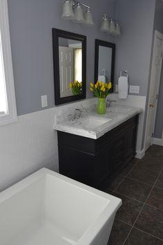 Grey, black and white bathroom. White soaking tub, white wainscotting, dark vanity and mirrors, grey countertop.