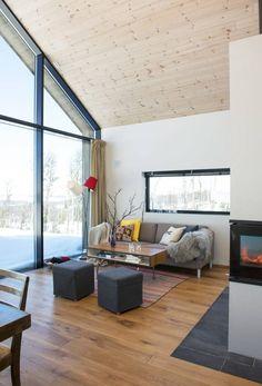 LYST OG ÅPENT: Hyttas hovedrom er stue og kjøkken i åpen løsning med en romslig hems over bakre del. Hele kortsiden er åpnet opp med vindu mot landskap og utsikt. Sofaen Arena er fra LK Hjelle. Lampen er fra 1960-tallet, arvet.