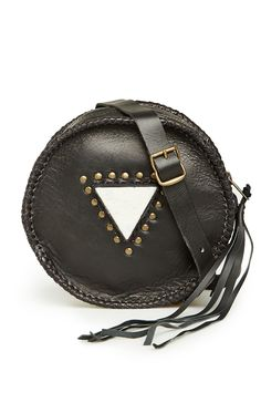 Round leather crossbody bag featuring a jade stone surrounded by metal studs on front, braided trim, fringe zipper-pull, and an adjustable buckled shoulder strap.