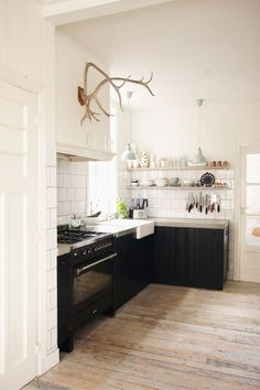 black & white kitchen. Love the rustic wood floors, the antlers, & the open shelves