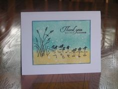 """By sillyfilly at Splitcoaststampers. On watercolor paper, use a waterbrush and spritzed ink on craft sheet to make a watercolor wash with two shades of blue for water and sky then golden brown for shore. Flick water onto card. Let dry. Stamp sandpipers and grasses from Stampin' Up """"Wetlands"""" in black. Stamp sentiment in black. Heat emboss or not."""