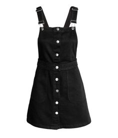 Black. Short bib overall dress in washed denim with adjustable suspenders, front pockets, and buttons at front.