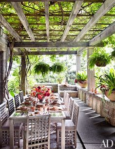 Kiwi vines shade a terrace furnished with a Charles Rennie Mackintosh–style teak table and chairs by R. L. White and Son.