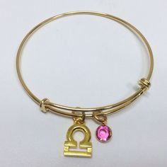 Libra- Balance, Beauty, TruthGold plated adjustable bangle with gold plated libra zodiac sign and swarovski october birthstone charms. #zodiac #bangle #gold #libra #october #ootd #pretty Available @ http://shareindipity-com.myshopify.com/collections/zodiac-collection/products/copy-of-gold-bangle-peace-charm