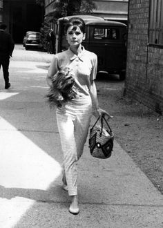 Busy-looking Audrey Hepburn juggles her dog, purse AND a cigarette in Paris, around mid-60's.