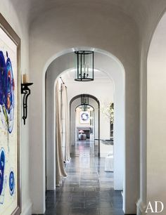 A large artwork by Francis hangs in the hallway, which is paved in antique Belgian bluestone; the Behnke-designed lanterns and the sconce are by Paul Ferrante.