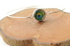 Peacock Bracelet - Peacock feather Cuff - Peacock eye Bracelet - Silver Bangle - Glass dome Bracelet - Nature Jewelry. €9.00, via Etsy.