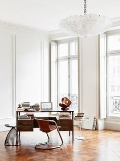 Open home office with high ceilings, a vintage desk, and a leather chair