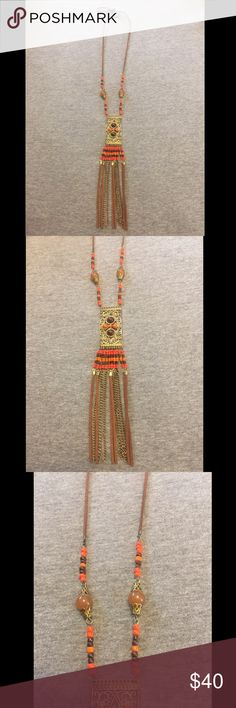 Bohemian Beaded Tassel and Pendant Rope Necklace This beautifully beaded tassel and rectangular pendant necklace is the perfect festival piece.  The pendant itself has a gold design accented with brown and orange beads. Tassels are beaded with gold chain and brown rope. There is no clasp so you can tie it at whichever length you'd like. Jewelry Necklaces