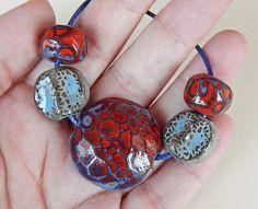 The set consists of =1 bead-lentil black ceramic , handcarved ,this bead are hollow and weigh very little , have red glaze , measures 30 x 30 mm. -4 beads hand-carved ,have red and blue glazes . By Mª Carmen Rodriguez Martinez ( Majoyoal ) https://www.facebook.com/groups/CeramicArtBeadMarket/