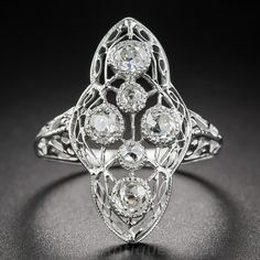 Edwardian Style Diamond Dinner Ring. Evoking the lightness and symmetry of fine antique Damask lace this Edwardian style ring measures 7/8 inch long dinner and showcases a half dozen scintillating mine-cut diamonds, totaling just shy of three-quarter carat. The bright-white stones are bezel-set with millegrain tooling seamlessly integrated into the woven tapestry of this low profile ring.