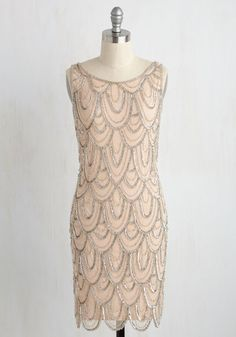 The celebration officially starts when you make your entrance in this beige shift dress! Mirroring an era of glamour and glee, this retro frock boasts clear beads and silver sequins that dazzle from the scooped back down to the scalloped hemline, bringing a flair to your fete that will stun for centuries.