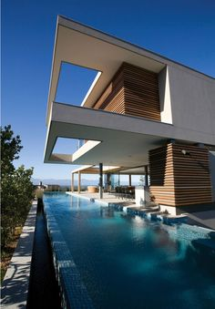 12 Modern Pools: Stefan Antoni Olmesdahl Truen Architects, also known as SAOTA, designed this six-bedroom beach house home in South Africa. The pool is long and linear, running closely alongside the terraced house, with an ocean view.
