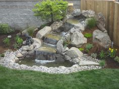 adorable waterfall ideas for backyard corner beside wooden fence including green grass in the nearby