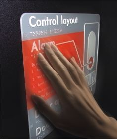Tactile signage on wall with braille, raised English, and audio
