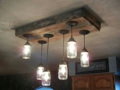 Rustic light fixture made with mason jars and old pallets.