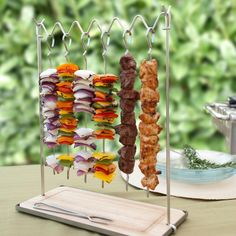 Stainless Steel Skewer Station. Present your grilled skewers in a dramatic fashion with this Stainless Steel Skewer Station from Charcoal Companion.  Allow your guests to personalize their entrees by choosing what they want from your array of single ingredient skewers.  Serving is simple by pushing the meat or vegetables down from skewers with the provided stainless steel fork onto a plate held underneath.  The wooden tray has grooves to prevent juices from spilling onto the table.