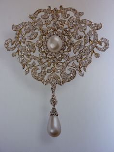 Queen Mary`s Richmond brooch; This quite large dramatic brooch was given to the future Queen Mary to mark her wedding to the Duke of York by the town of Richmond. The Teck family were long time residents at White Lodge in Richmond Park. The brooch is made of gold, set with diamonds framing a large central pearl & can be worn with or without the pearl drop. The Queen inherited the brooch from Queen Mary in 1953.