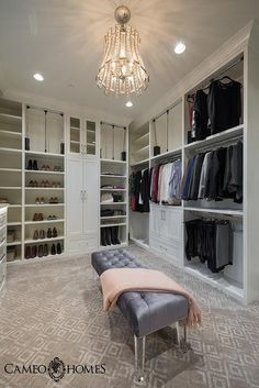 Spacious gray walk-in closet showcase a gorgeous gray tufted bench on lucite legs sat on a gray diamond print rug illuminated by a chic nickel and glass pendant.