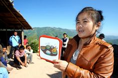 Plan Laos WASH officer Nali Senthavong uses flash cards to teach the community about the health problems caused by going to the toilet in the open.