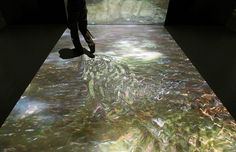 A visitor walks on a floor with a projection resembling water using Solidray Co's projector system Tap Talk 2, which reacts to people's movements on a virtual image, at the Digital Content Expo 2009 in Tokyo