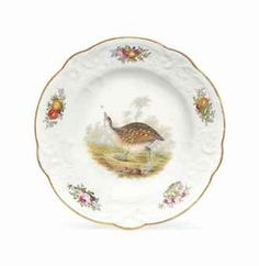 A NANTGARW (LONDON-DECORATED) ORNITHOLOGICAL SOUP-PLATE  CIRCA 1817-18, IMPRESSED NANTGARW/C.W. MARK, TITLED IN IRON-RED SCRIPT  Almost certainly painted in the workshop of John Bradley, with a study of a Landrail in wooded landscape vignette, the C-scroll moulded border enclosing bouquets of garden flowers alternating with fruits on a bed of leaves, within a shaped gilt dentil rim  9½ in. (24.2 cm.) wide