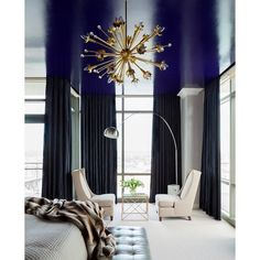 An ultra high-gloss ceiling in a bold color adds instant drama to this space. Interior Design: Tobi Fairley Paint: Benjamin Moore Midnight Navy Chandelier: Jonathan Adler Sputnik Chandelier Floor Lamp: Nuevo Cora White Floor Lamp
