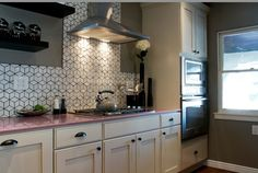 Geometric tile and a light pink countertop add depth and interest to an otherwise subdued kitchen. Kitchen Cousins Season 2