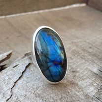 A stunning, elegant, bold labradorite cabochon has been set in sterling silver. This large oval labradorite stone is a bright blue with flashes of green, yellow, pink, and reds. It is a beautiful luminescent stone. The natural black gradient lines in the labradorite highlight the colors. This sto...