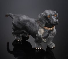 Black Obsidian Carving of a Dachshund By the House of Fabergé Jewelry Salon St. Petersburg, Russia Obsidian depicting of a daschund. The cabochon eyes are carved of Ukrainian yellow heliodor. The diamond accented collar is of 14K yellow gold and the toenails are of yellow gold. Length 4 1/4in Footnotes      Accompanied by a certificate from the House of Fabergé Gold Collection, St. Petersburg, Russia