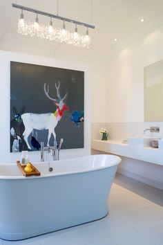 love the white, the art, the freestanding tub and the lighting