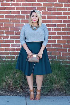 A model with curves wearing a beautiful teal skirt and grey sweater, great blend and fashion statement with copper beige shoes.
