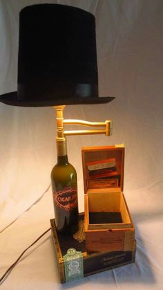 The Gentleman table lamp-   Just like the perfect blend in your favorite wine, we brought you a sleek bottle that holds its head/light high and because he's a true gentleman, it can swivel to extend its hat. And for convenience we've included a nifty cigar box that doubles as a small hiding place for all of your important items.  http://www.twiceconsign.com/