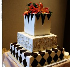 The cake was iced in cream-colored buttercream and covered with a chocolate brown diamond pattern and gold scrollwork. On top, an arrangement of fresh flowers tied in the cake with the rest of the reception decor.