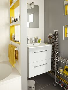 Une cloison creusée en niches pour ranger et séparer baignoire et vasque dans la salle de bains