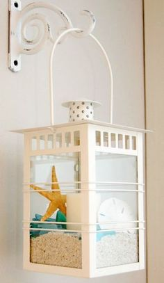 Fabulous ideas for creating beach lanterns. Regular lanterns used (and made over) to display beach finds.