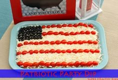Patriotic Party Dip - 7 layer dip decorated like a flag using white cheese (mozzarella, Monterrey Jack, etc.), grape tomatoes, and black olives.
