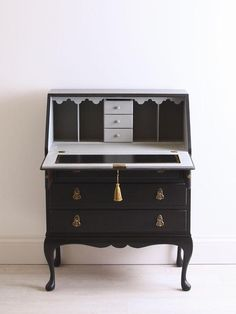 Meet Beau – he's a beautiful black bureau painted with Annie Sloan's Graphite Chalk Paint on the exterior and Paris Grey Chalk Paint on the interior. A new black leather inlay has been fitted with gold gilding around the edges. New black fine felt strips have been added to the arm rests too. A key has been cut for the lock on the desk and I've hung a gold tassel from it for an elegant finish. I've also brushed a little gold leaf here and there for a final flourish. Let me know what you think.