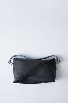 Acne Studios Rope Messenger black/light blue is a leather shoulder or cross body bag with large whipstitch details.