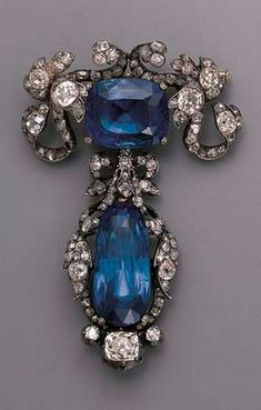 AN ANTIQUE SAPPHIRE AND DIAMOND BROOCH  Designed as a cushion-cut sapphire within an old-cut diamond foliate mount, suspending a detachable drop-shaped sapphire within similar mount, mounted in silver and gold, circa 1870, 6.0 cm. high, in original black case by Nativelle, Paris