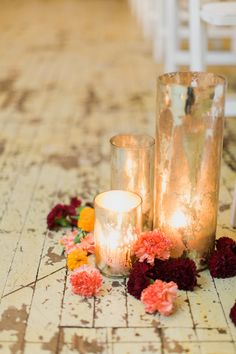 candles and flowers down aisle. but these candles are too vintage-y. i'd do a clean, modern votive and let the pretty venue shine on its own