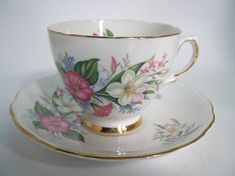 Beautiful tea cup and saucer made by Colclough England White set with pink and white flowers. The backstamp date this tea cup 1955 - 1964 The tea cup is 2 3/4 high and the saucer is 5 5/8 diameter The rims are gilt. Very good condition, no chips, no hairline and no gold loss, and
