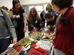 """SDA Swatch Collections Offer Encyclopedic View of *Surface Design*. Attendees at """"Surface Matters"""" Washington State Symposium (2012) enthusiastically peruse SDA Swatch Collections. Photo by Jane Dunnewold"""